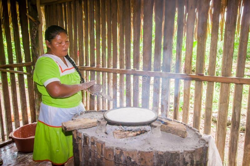 LAGO AGRIO, ECUADOR - NOVIEMBRE, 17 2016: La mujer demuestra cocinar las tortillas de la yuca en dentro una cocina en un Siona foto de archivo libre de regalías