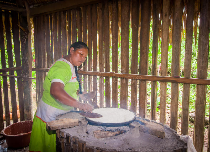 LAGO AGRIO, ECUADOR - NOVIEMBRE, 17 2016: La mujer demuestra cocinar las tortillas de la yuca en dentro una cocina en un Siona imágenes de archivo libres de regalías