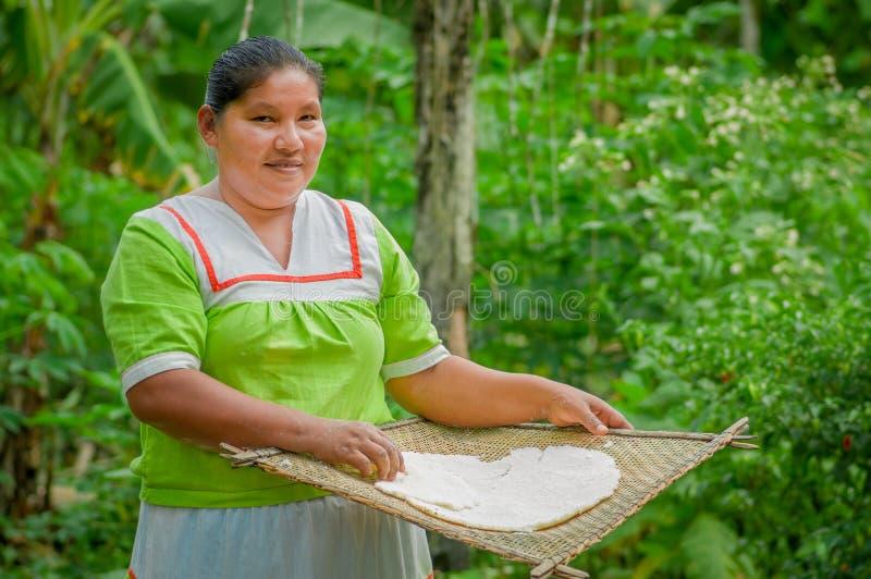 LAGO AGRIO, ECUADOR - NOVIEMBRE, 17 2016: La mujer demuestra cocinar las tortillas de la yuca en una cocina al aire libre en un S fotografía de archivo libre de regalías