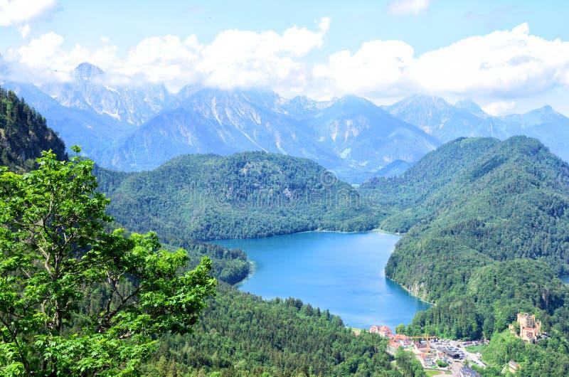 Lago alpino e a vila de Hohenschwangau perto de Fussen no sudoeste Baviera, Alemanha fotos de stock
