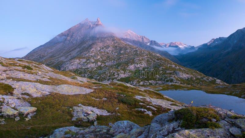 Lago alpino high altitude in terra idilliaca con i picchi di montagna rocciosa maestosi Esposizione lunga al crepuscolo Vista gra immagine stock libera da diritti