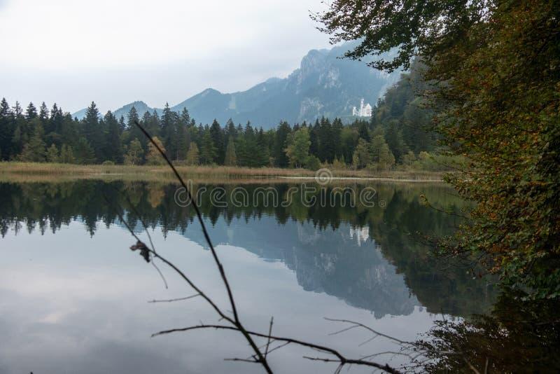 Lago alpino, Schwansee no fundo o castelo famoso Neuschwanstein na montanha com reflexão na água imagens de stock