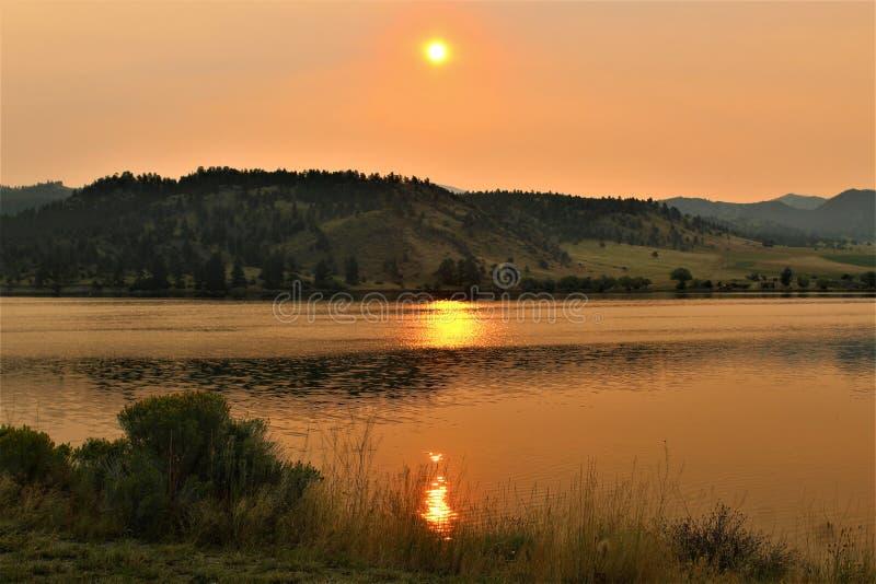 Lago anaranjado de oro del espejo de la salida del sol de la montaña de Montana foto de archivo