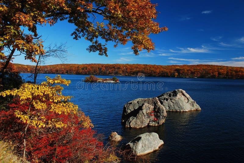 Lago autumn com rochas e árvores imagem de stock royalty free