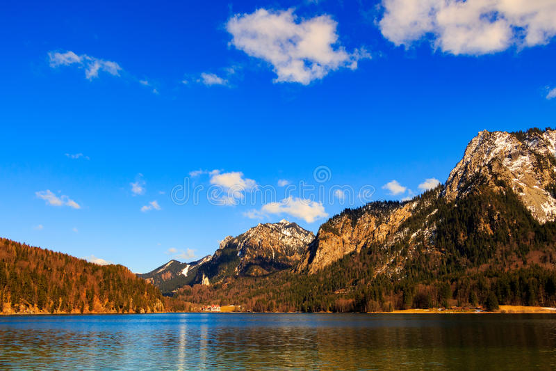 Lago azul Alpsee na floresta verde e nas montanhas bonitas dos cumes Fussen, Baviera, Alemanha imagem de stock