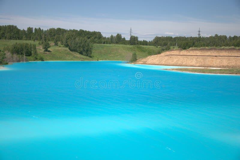 Lago azul com as costas arenosas altas cobertos de vegetação com a paisagem conífera da floresta imagem de stock