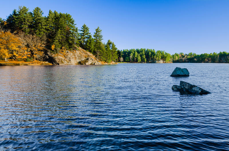 Lago azul con las rocas y árboles y Autumn Foliage imagenes de archivo
