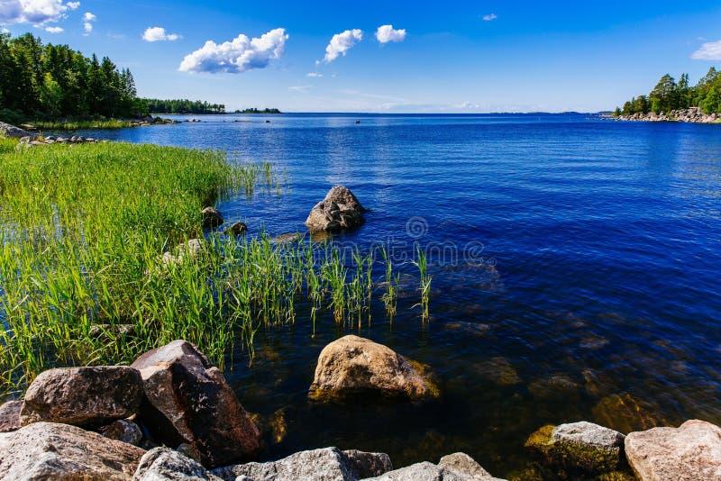 Lago azul da água clara com pedras e floresta verde em um dia de verão ensolarado em Finlandia imagem de stock royalty free