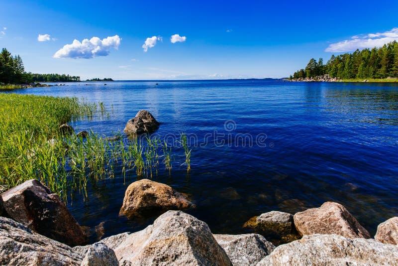 Lago azul da água clara com pedras e floresta verde em um dia de verão ensolarado em Finlandia imagem de stock