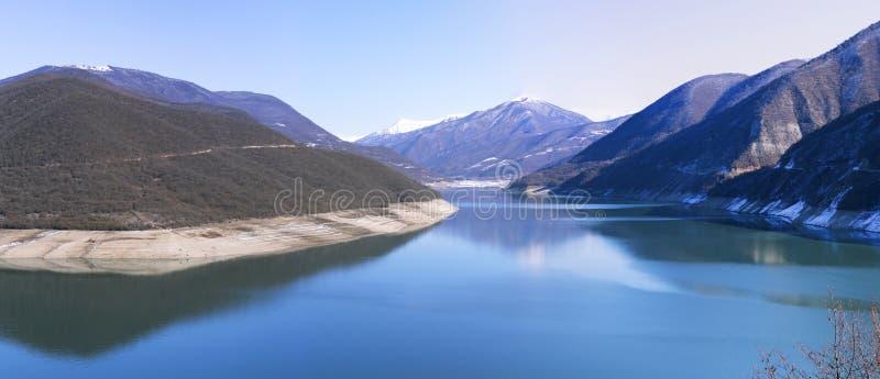 Lago azul en las montañas contra los picos nevosos fotos de archivo