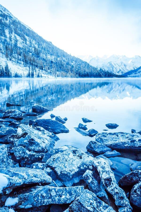 Lago azul hermoso en las montañas Superficie plana del espejo del agua debajo de las nubes imágenes de archivo libres de regalías
