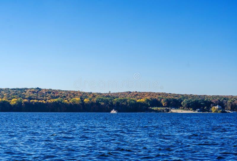 Lago azul Pequeño barco de placer en el fondo del bosque foto de archivo libre de regalías