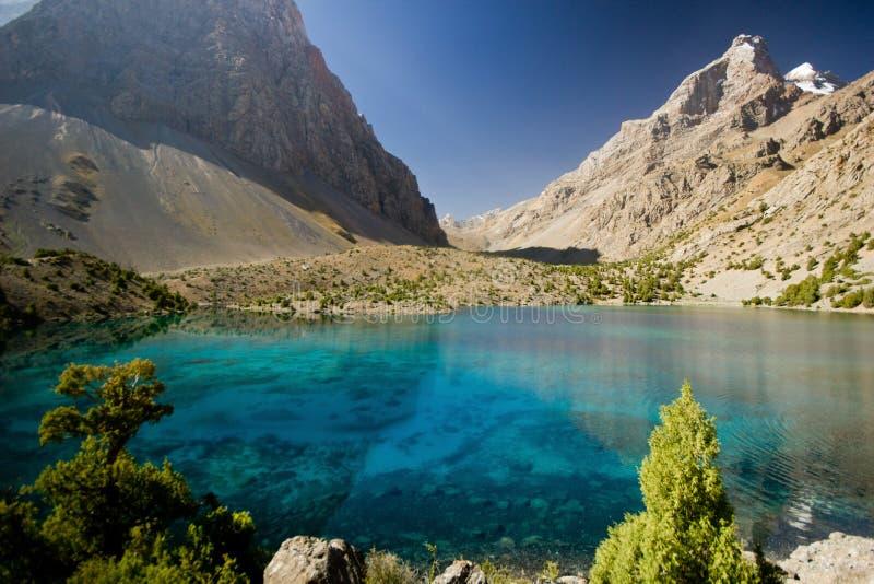 Lago azul profundo en las montañas de Fann en la salida del sol imagen de archivo