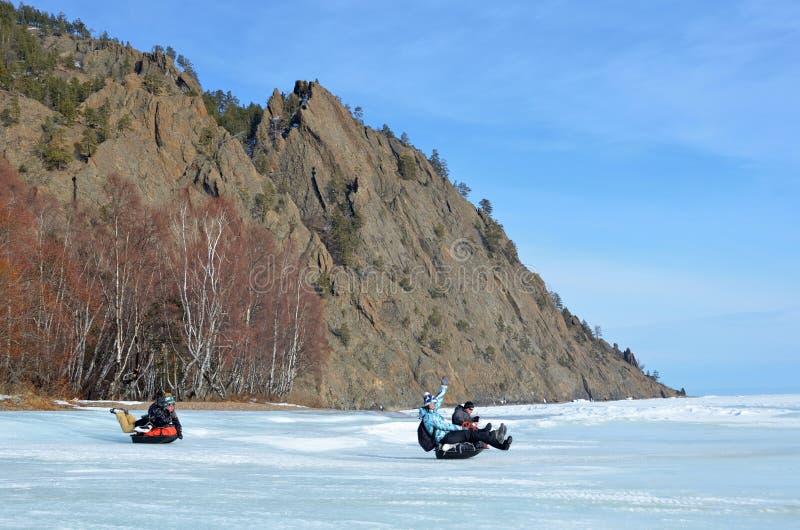 Lago Baikal, Rússia, março, 01, 2017 Turistas que montam em costas geladas de um MS dos pequenos trenós do trenó do Lago Baikal imagem de stock