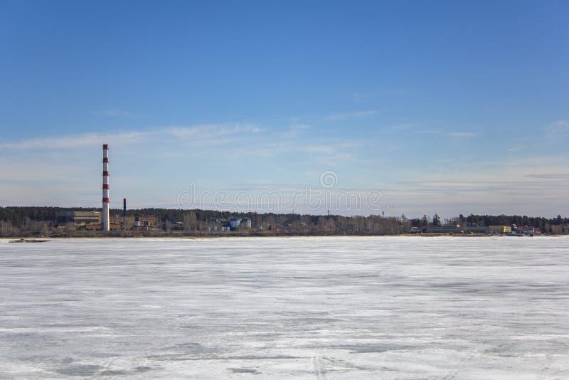 Lago bianco congelato della neve sui precedenti di una pianta con un tubo rosso a strisce, le costruzioni ed i magazzini in una f fotografie stock libere da diritti