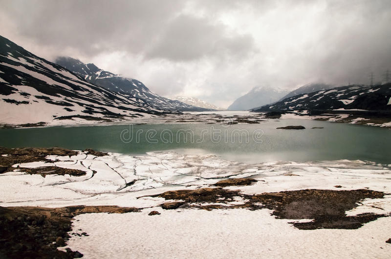 Lago Bianco with snowy mountains and green water in lake, Bernina pass,Switzerland stock photos