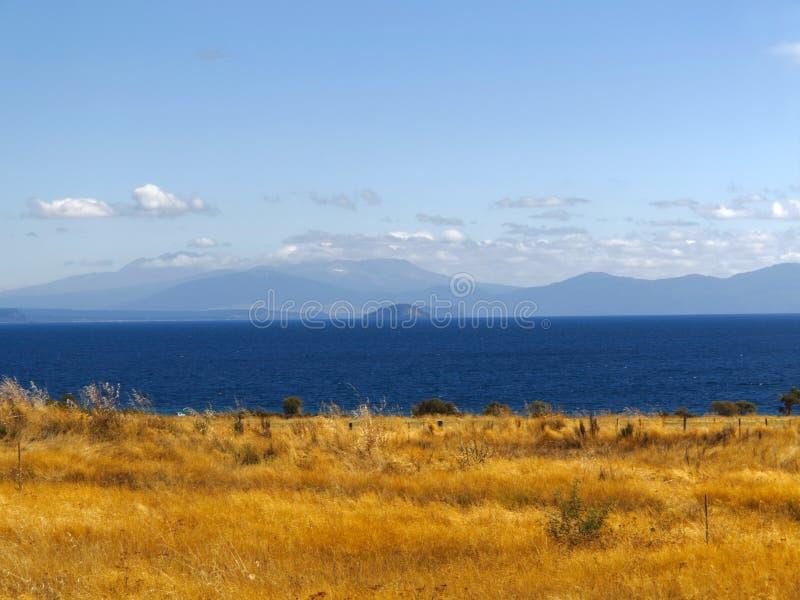 Lago blu calmo Montagne blu coperte dalle nuvole Riva dorata di Fied dell'erba fotografia stock