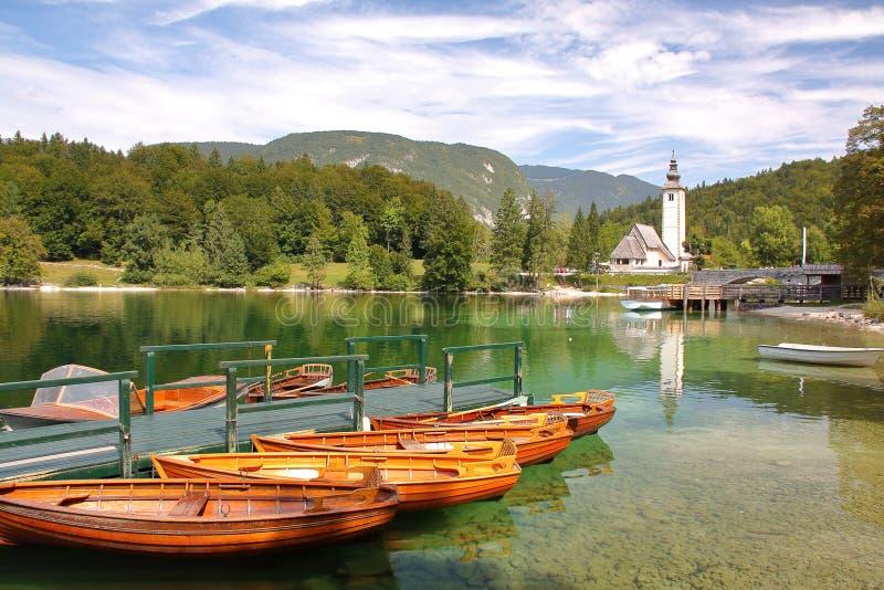 LAGO BOHINJ, ESLOVÊNIA - 10 DE SETEMBRO DE 2012: Lago Bohinj com a igreja de St John o batista no fundo imagem de stock royalty free