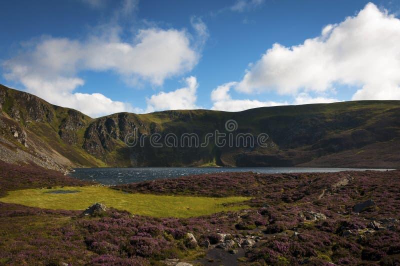 Lago bonito cercado por penhascos e por montanhas nas montanhas de Escócia em Reino Unido imagem de stock