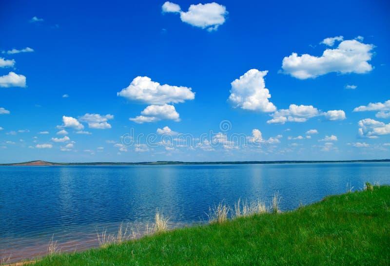 Lago, céu nebuloso azul e grama verde fotografia de stock