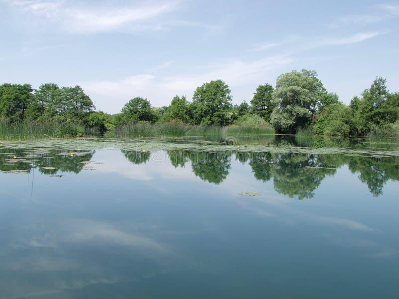 Lago calmo com as nuvens refletidas na água imagens de stock