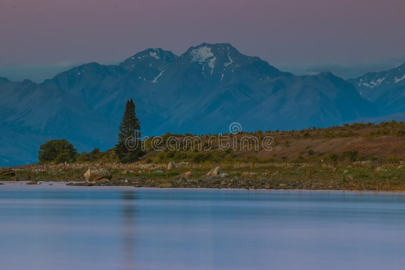 Lago calmo con la riva rocciosa fotografia stock libera da diritti