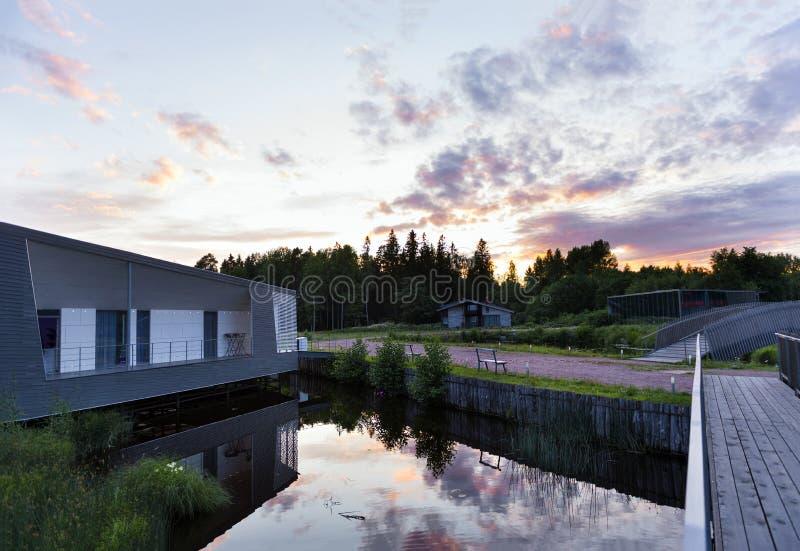Lago, casa de férias, noites brancas no norte, o céu com as nuvens lilás refletidas na água fotografia de stock