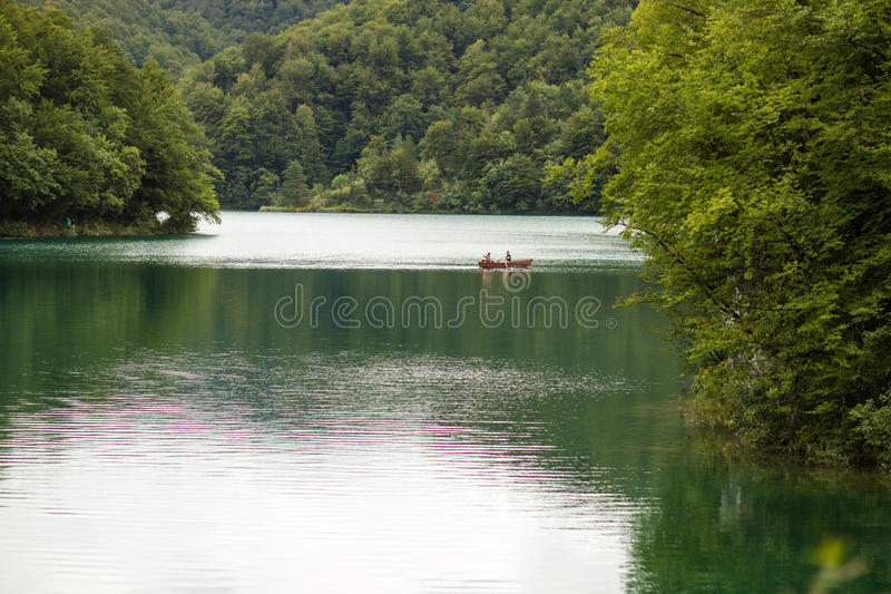 Lago circondato dalle montagne verdi immagine stock