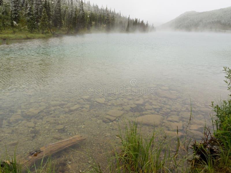 Lago claro de la montaña que cuece al vapor después de nevadas del verano imagen de archivo libre de regalías