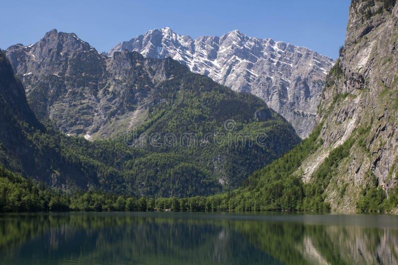 Lago com as montanhas claros da água na primavera Um lago pequeno na opinião dos cumes de uma costa Reflexão das montanhas dentro imagem de stock
