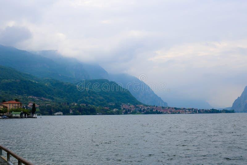 Lago Como con los edificios en la costa costa, montaña de las montañas con las nubes en fondo imagen de archivo