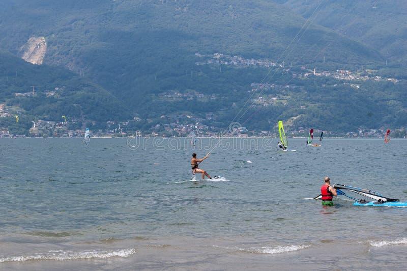 Lago Como, Italia - 21 luglio 2019 Sport acquatici: i kitesurfers ed i windsurfers stanno praticando il surfing il vento sulle on fotografia stock