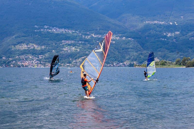 Lago Como, Italia - 21 luglio 2019 Sport acquatico: un gruppo di tre windsurfers che praticano il surfing il vento sulle onde un  fotografie stock libere da diritti