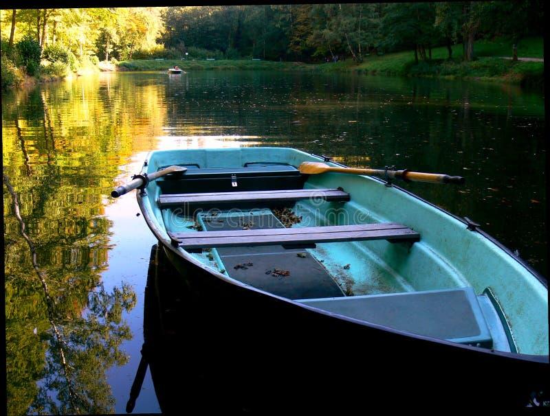 Lago con el barco que rema azul y reflexión amarilla en el agua fotos de archivo