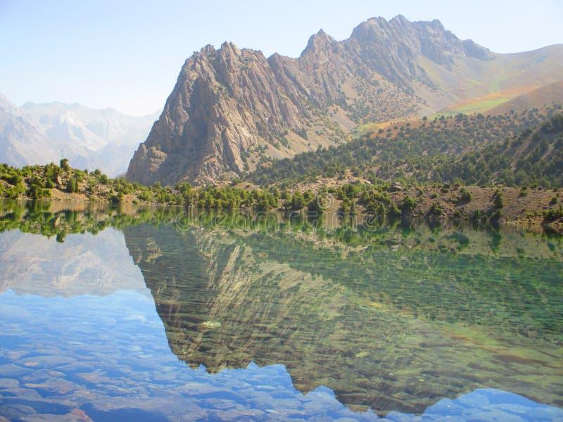 Lago con la riflessione dei picchi di montagna immagine stock