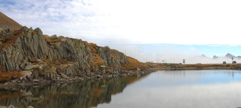 Lago con la riflessione della roccia sopra il passaggio di Grimsel in Svizzera immagini stock libere da diritti