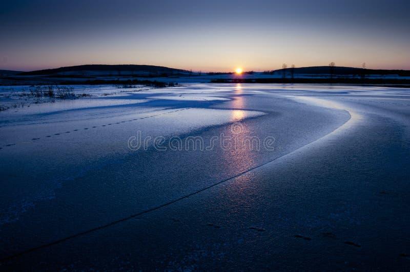 Lago congelado con puesta del sol en invierno fotografía de archivo libre de regalías