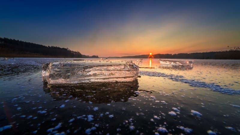 Lago congelado hermoso del invierno con el pedazo de hielo en la puesta del sol fotografía de archivo