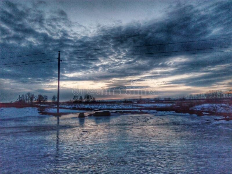 Lago congelato e belle nuvole immagine stock