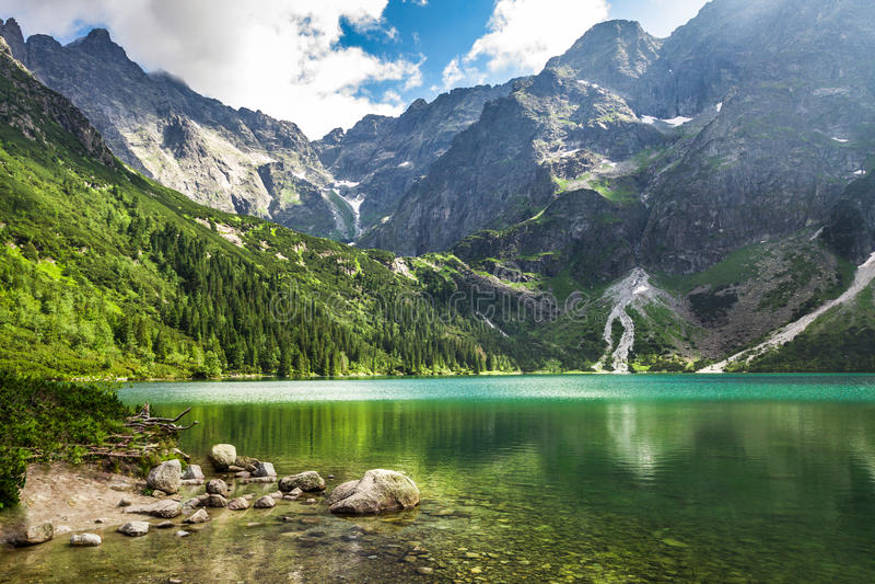 Lago cristalino de la montaña y montañas rocosas foto de archivo libre de regalías