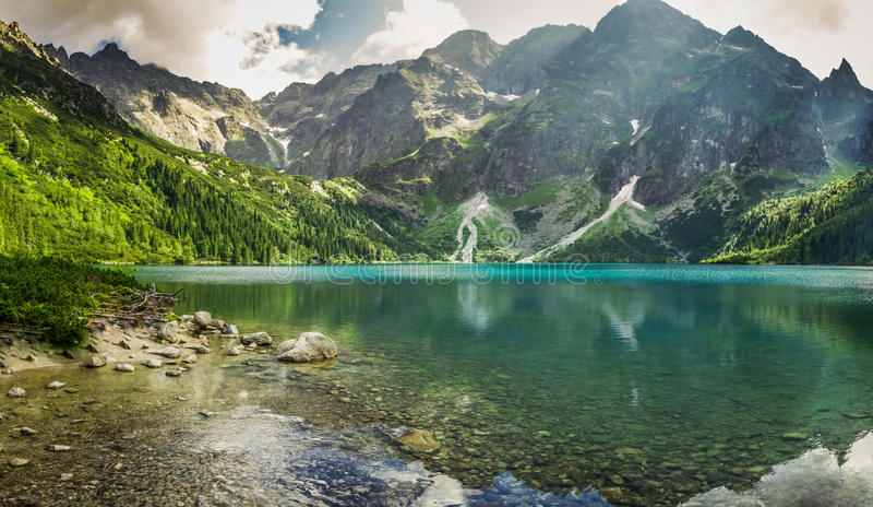 Lago cristalino de la montaña y montañas rocosas foto de archivo