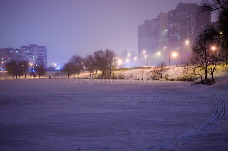 Lago da cidade do inverno na noite lago Gelo-coberto e lanternas leves alaranjadas fotos de stock royalty free