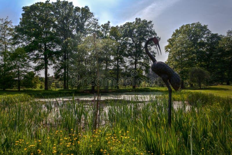 Lago de bronze do junco da garça-real da estátua, parque do arboreto, Wespelaar, Lovaina, Bélgica foto de stock