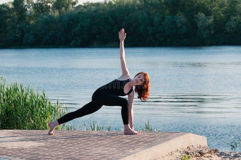Lago de la salida del sol de la yoga de la belleza de la muchacha al aire libre fotos de archivo libres de regalías