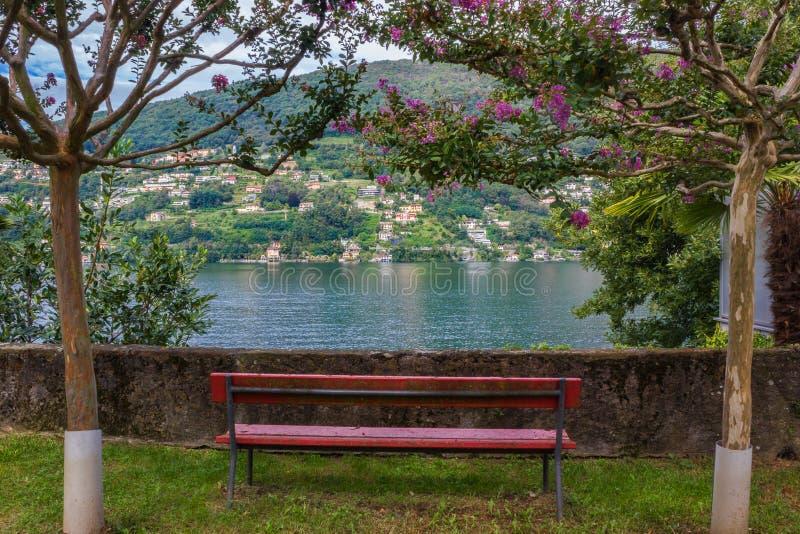 Lago de negligência Lugano bench vermelho em Suíça imagens de stock