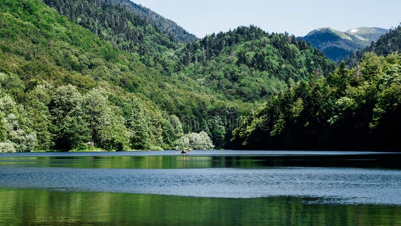 Lago del biogradsko de la foto con la flotación de él con los viajeros en el barco fotos de archivo libres de regalías