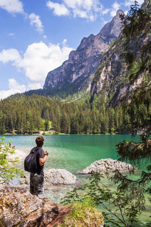 Lago Di Braies, Italië - Juni 1, 2018: De jonge kerel, een toerist met een rugzak bevindt zich op de kust van het meer en bekijkt stock foto's