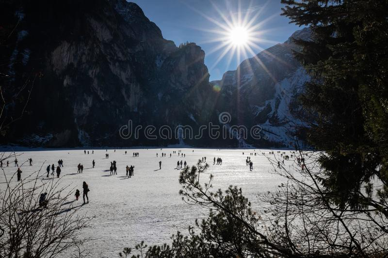 Lago di Braies, Italy - January 1, 2019: people having fun ice skating and hiking on frozen lake lago di braies for the first day royalty free stock photos