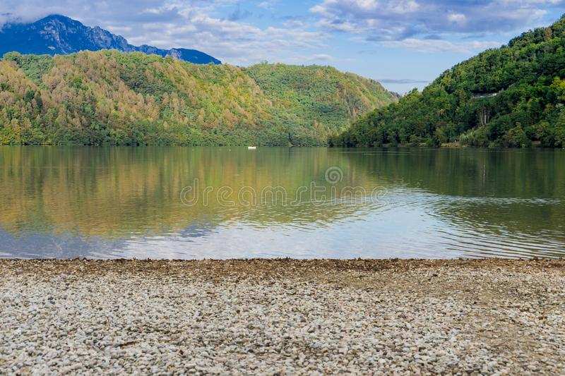 Lago di Levico, Lake in Levico Terme, Italy. Mountains, woods, water and pebbles in spa town Levico Terme, Italy, Europe royalty free stock photography