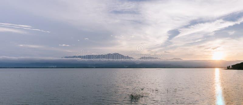 Lago e montanha bonitos durante a paisagem do por do sol no panorama no lago Phayao fotos de stock